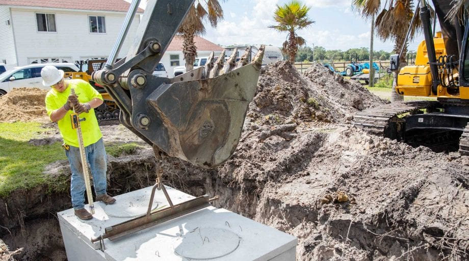 Wind River employees using an excavator to level a septic tank